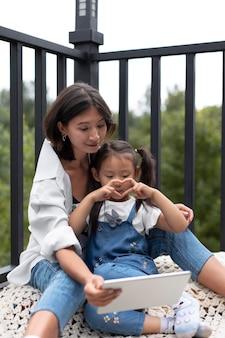 Vrouw heeft een videogesprek met haar man naast hun dochter buitenshuis