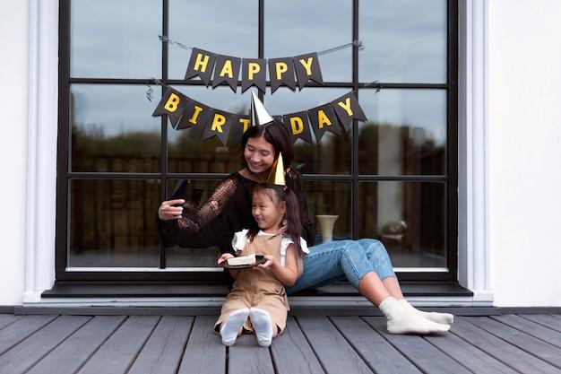 Vrouw heeft een videogesprek met haar man op de verjaardag van hun dochters