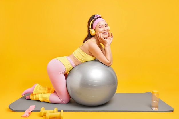 Vrouw heeft fitnesstraining met zwitserse bal glimlacht aangenaam gekleed in sportkleding luistert muziek via koptelefoon maakt gebruik van sportuitrusting