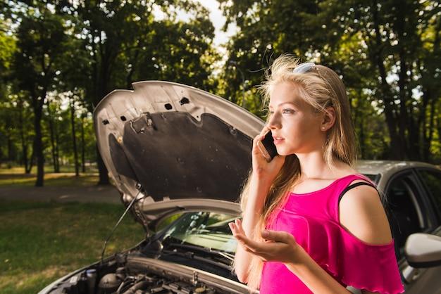Vrouw heeft gesprek over kapotte auto