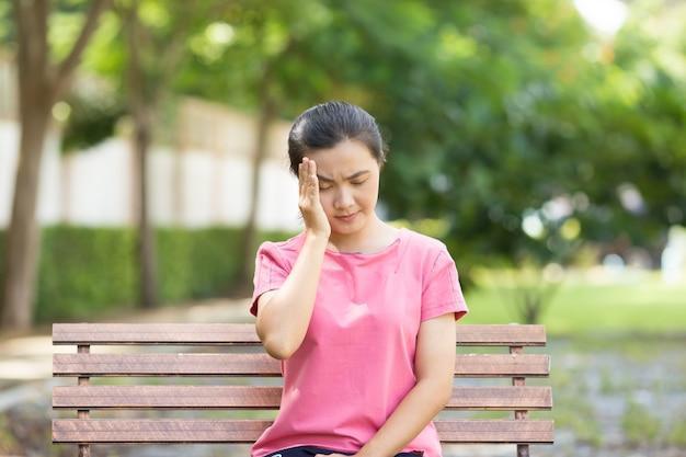Vrouw heeft hoofdpijn in de tuin