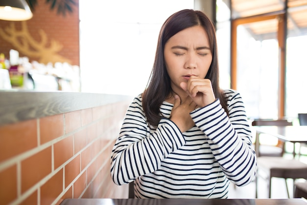 Vrouw heeft keelpijn in het café