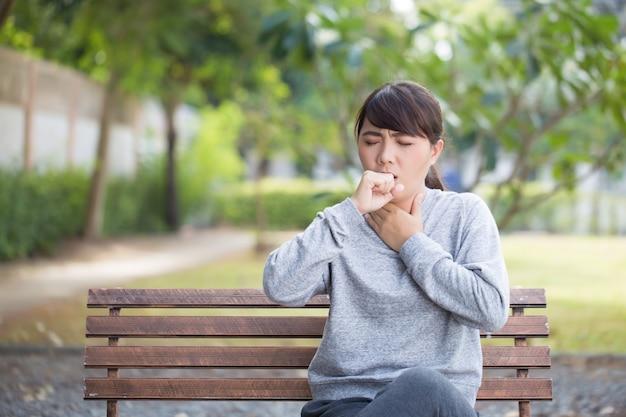 Vrouw heeft keelpijn in het park