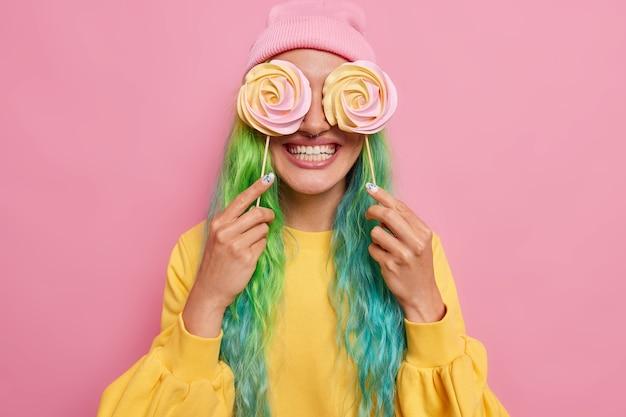 Vrouw heeft kleurrijk haar tegen ogen met karamel snoep glimlacht breed heeft zoetekauw geniet van cheat meal dag dwazen rond draagt vrijetijdskleding poseert op rooskleurig