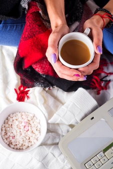Vrouw heeft koffie, koopt cadeautjes, bereidt zich voor op kerstavond, zit tussen marshmallow en gezellige plaid. kerstvakantie