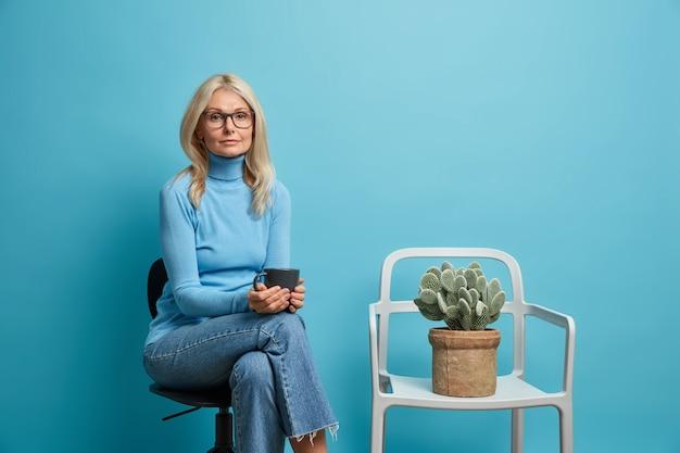 Vrouw heeft koffiepauze drinkt drank uit beker poseert op comfortabele stoel op blauw