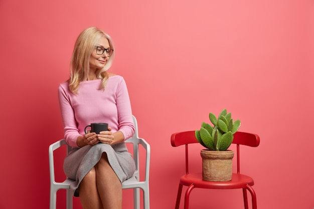 Vrouw heeft koffiepauze houdt mok drank vast kijkt aandachtig naar potcactus zit op stoel geïsoleerd op roze