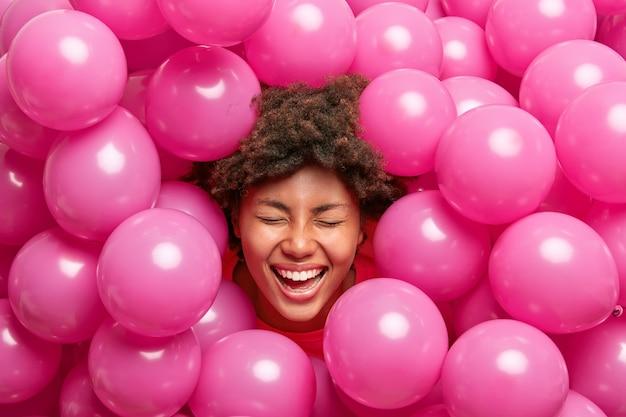 Vrouw heeft krullend haar dwaas rond glimlacht breed met witte tanden houdt ogen dicht steekt hoofd uit kleine roze ballonnen.