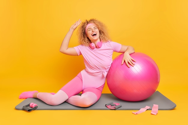 Vrouw heeft krullend haar houdt arm omhoog lacht vrolijk heeft een opgewekt humeur na fitnesstraining poseert op mat met fitball-weerstandsbanden