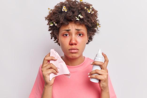 Vrouw heeft krullend haar met vastzittende kamillebloemen houdt neusspray vast en servet gekleed in roze t-shirt heeft last van neus en roodheid