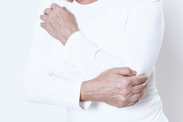Vrouw heeft pijn in haar arm in witte kamer.