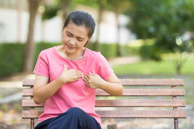 Vrouw heeft pijn op de borst in de tuin