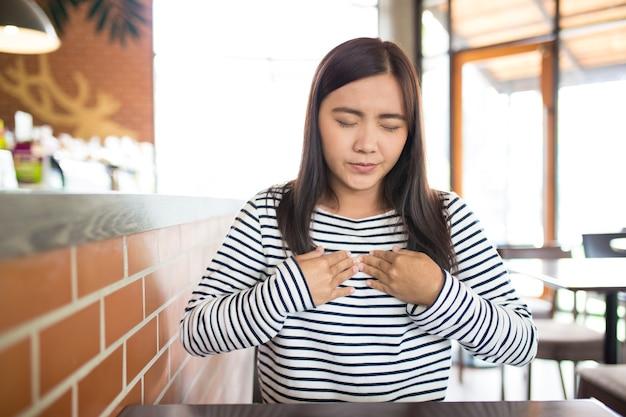 Vrouw heeft pijn op de borst in het café