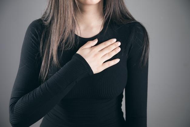 Vrouw heeft pijn op de borst op grijze achtergrond