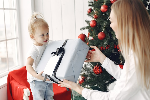 Vrouw heeft plezier met het voorbereiden van kerstmis. moeder in een wit overhemd speelt met haar dochter. familie rust in een feestelijke kamer.