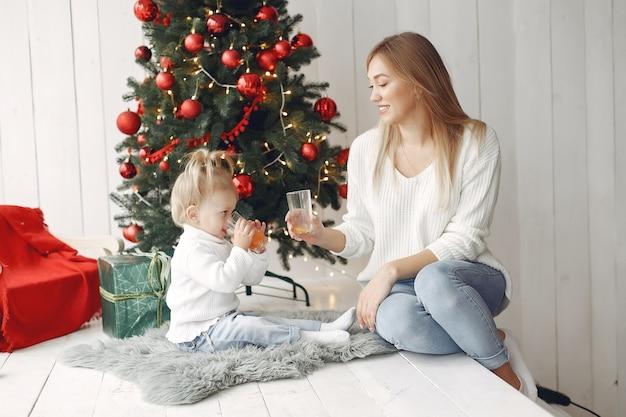 Vrouw heeft plezier met het voorbereiden van kerstmis. moeder in witte trui spelen met dochter. familie rust in een feestelijke kamer.