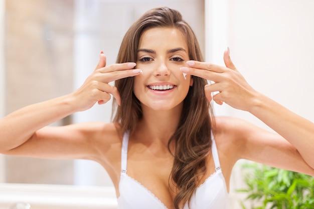 Vrouw heeft plezier tijdens het aanbrengen van een vochtinbrengende crème op het gezicht