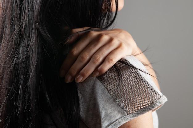 Vrouw heeft schouderpijn op grijze achtergrond Premium Foto