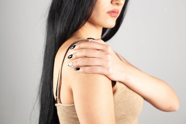 Vrouw heeft schouderpijn op grijze achtergrond