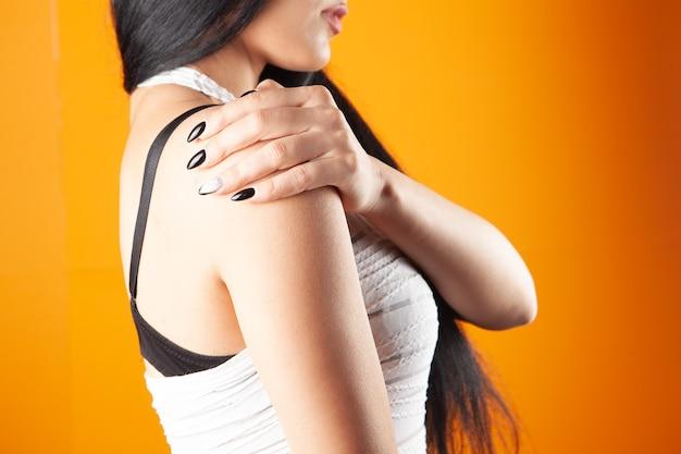 Vrouw heeft schouderpijn op oranje achtergrond