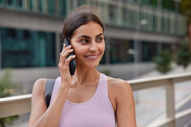 Vrouw heeft telefoongesprek bespreekt haar plannen met vriend maakt plannen voor de dag heeft een positieve uitdrukking glimlacht loopt zachtjes naar buiten op wazig