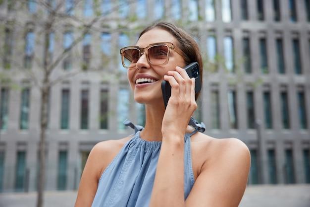 Vrouw heeft telefoongesprek tijdens het zwerven voelt zich blij geniet van wandelingen in architecturale stad praat via de telefoon draagt een zonnebril tijdens zonnige dag poseert buitenshuis