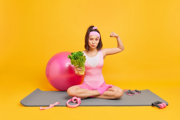 Vrouw heft arm toont spieren na training houdt zich aan gezonde voeding houdt groente zit gekruiste benen op fitnessmat met sportuitrusting eromheen. gezonde levensstijl