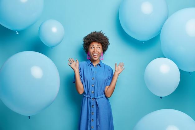 Vrouw heft handpalmen op, gekleed in feestelijke jurk kijkt boven geïsoleerd op blauw