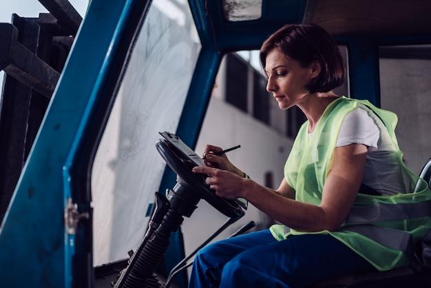 Vrouw heftruck operator document in het voertuig te ondertekenen