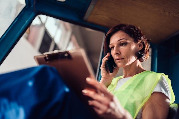 Vrouw heftruck operator document lezen en praten over de telefoon