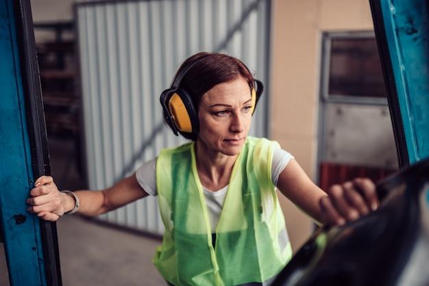 Vrouw heftruck operator voertuig invoeren