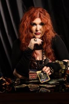 Vrouw heks, waarzegster met rood haar voert een magisch ritueel uit. kaart lezen.