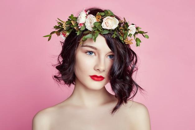 Vrouw heldere zomer ziet er mooie kleren uit. bloemenkrans op het hoofd. brunette meisje poseren en lachend op helder roze achtergrond. dame met bloemen