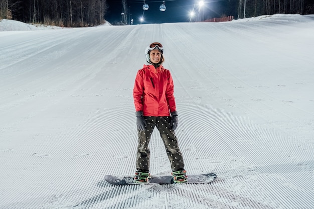 Vrouw helm met snowboard dragen op de skipiste. avond rijden