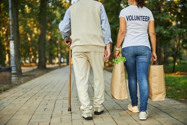 Vrouw helpt met papieren boodschappentassen aan de oude man