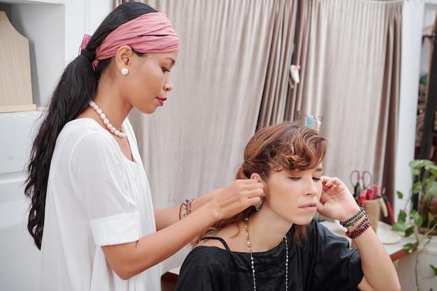 Vrouw helpt oorbellen te zetten