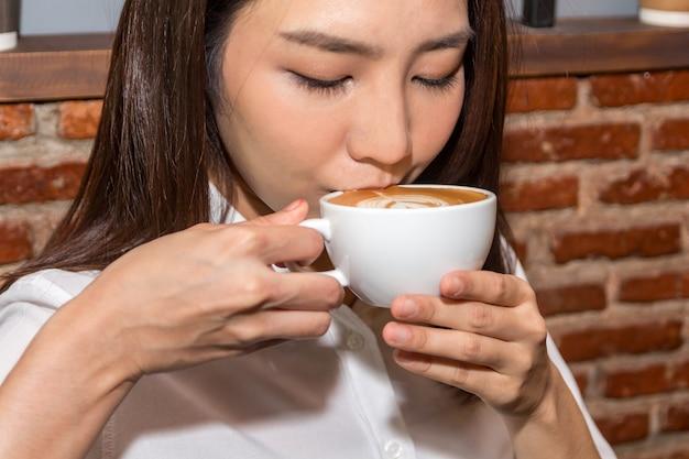Vrouw het drinken koffie bij koffiewinkel