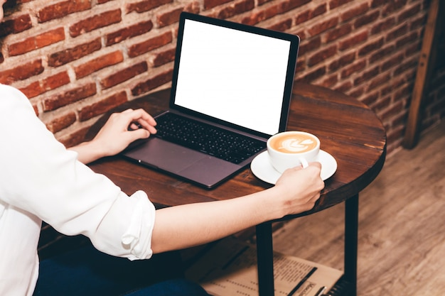 Vrouw het drinken koffie en het werk aan laptop computer bij koffiewinkel