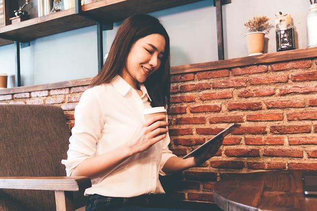 Vrouw het drinken koffie en het werk aan tablet bij koffiewinkel