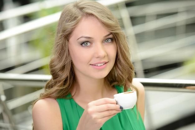 Vrouw het drinken koffie in de ochtend bij restaurant.