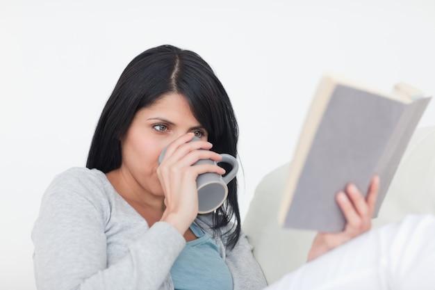 Vrouw het drinken van een grijze mok terwijl het lezen van een boek
