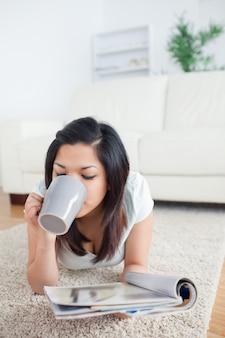 Vrouw het drinken van een mok terwijl het houden van een tijdschrift