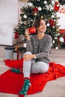 Vrouw het drinken van thee op kerstavond