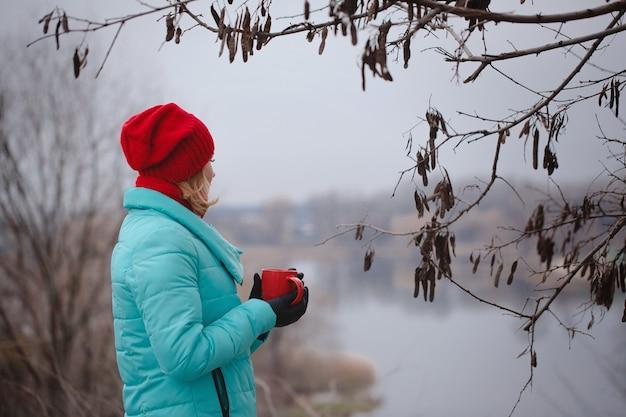 Vrouw het drinken van thee uit een rode kop