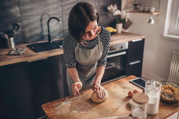 Vrouw het kneden deeg op de houten lijst