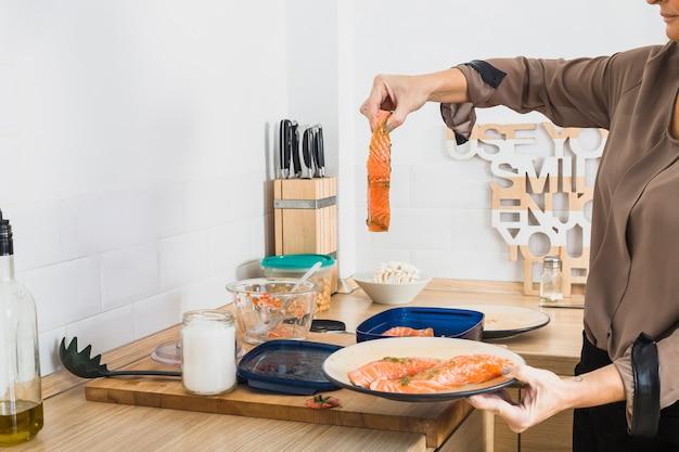 Vrouw het koken visschotel in keuken