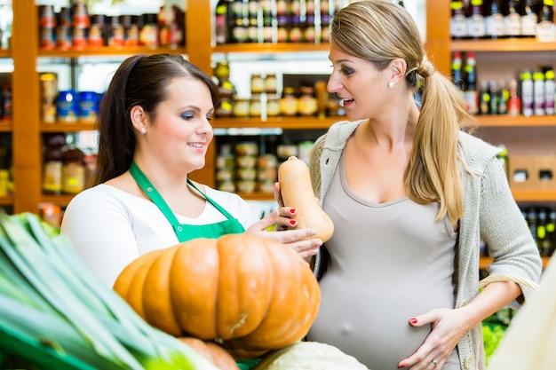 Vrouw het kopen pompoen en groenten in delicatessen