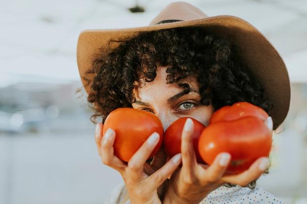 Vrouw het kopen tomaten bij een landbouwersmarkt