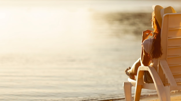 Vrouw het leggen sunbed kijkend op zee