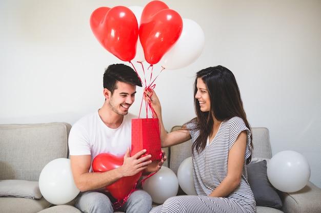 Vrouw het leveren van haar vriendje ballonnen en een rode zak